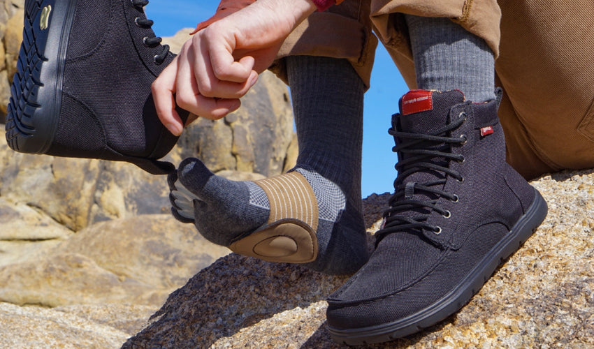 A seated hiker in the high country wearing toe spacers, toe socks, and metatarsal pads and donning a pair of Lems Boulder Boots