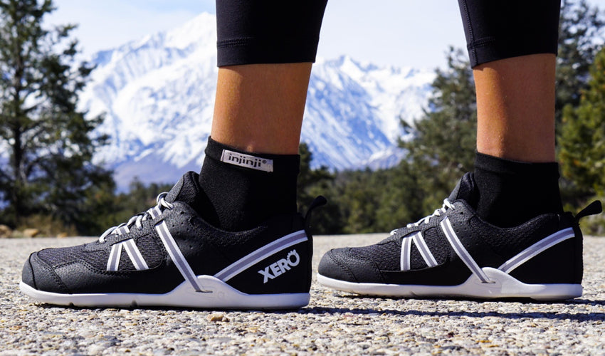A side view of Xero Prio athletic shoes worn by a road runner with snowy mountains in the background