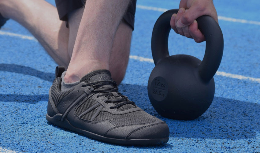 An athlete kneeling on a blue track with a kettlebell and wearing Xero Prio athletic shoes