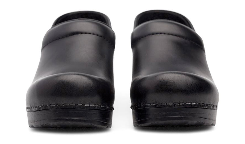 A head-on view of a pair of conventional black clogs against a white background