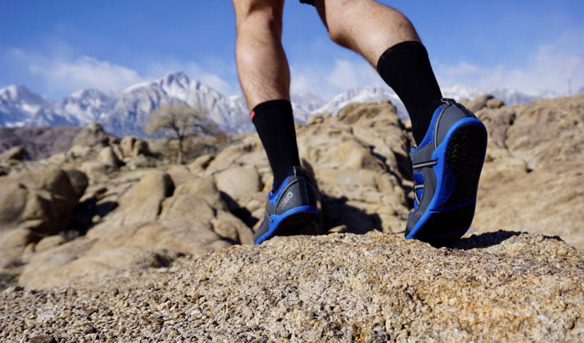 An athlete wearing Xero Prio athletic shoes and running toward a group of snowy mountains