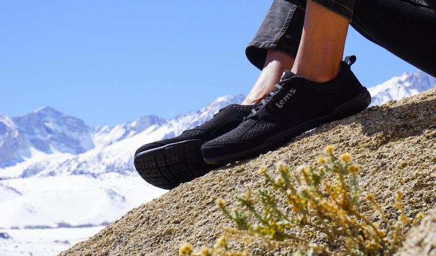 A person wearing Lems Primal 2 Black shoes and sitting on a rocky outcropping with snowy peaks in the background