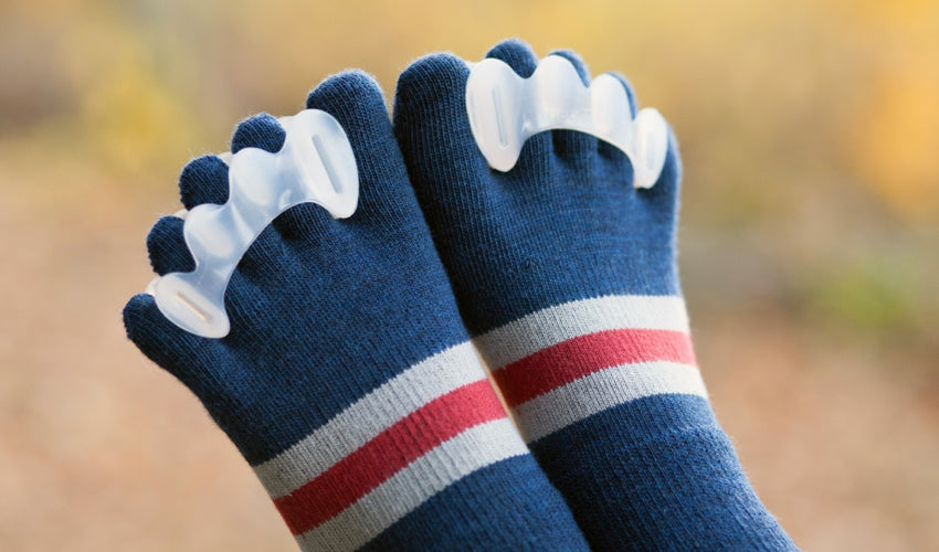 A close-up shot of a person wearing Correct Toes toe spacers and Injinji toe socks with fall colors in the background