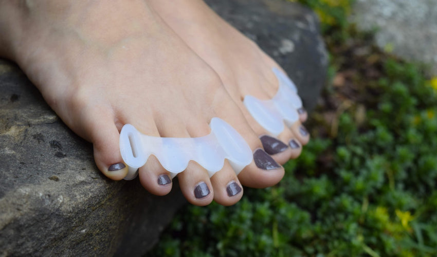 Close-up shot of Correct Toes Original toe spacers on bare feet overhanging a stone step in a garden setting