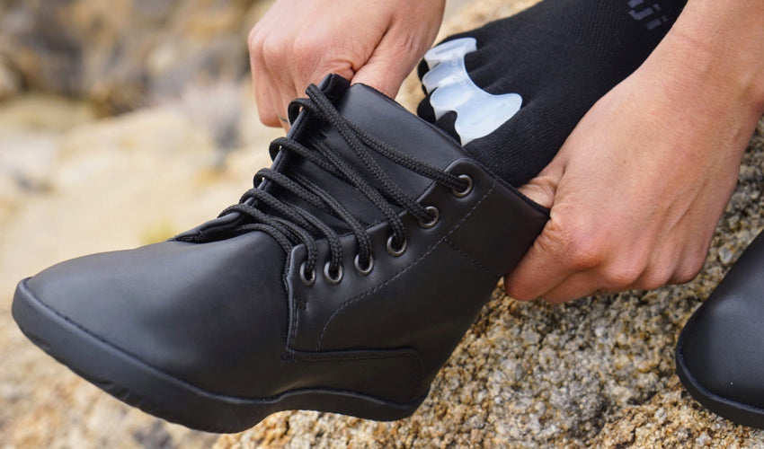 A hiker wearing Correct Toes toe spacers while putting on Ahinsa Trek Bare Ankle boots