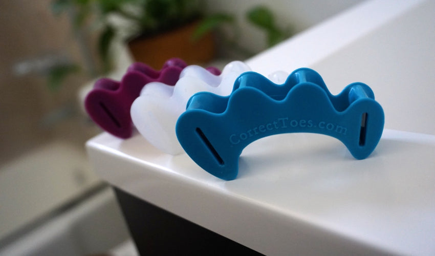 Three colors of Correct Toes toe spacers lined up in a row: Aqua, Original, and Plum