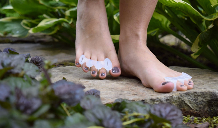 A person wearing Correct Toes on bare toes and walking over flat stones in a garden setting