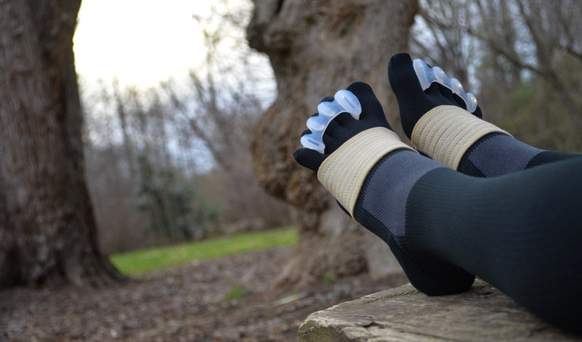 A person wearing Correct Toes and other natural footgear while stretching out their legs on a park bench