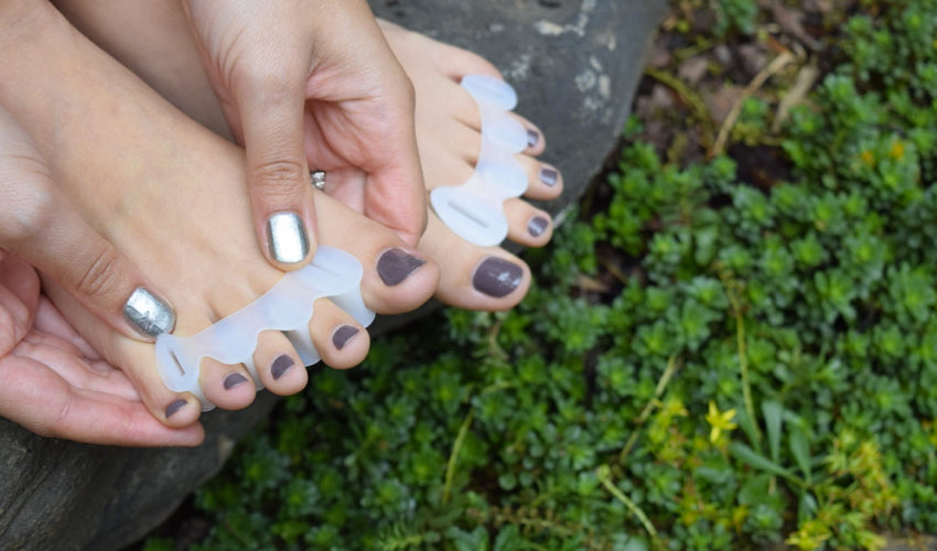 A person applying Correct Toes Original toe spacers on bare toes in a garden setting