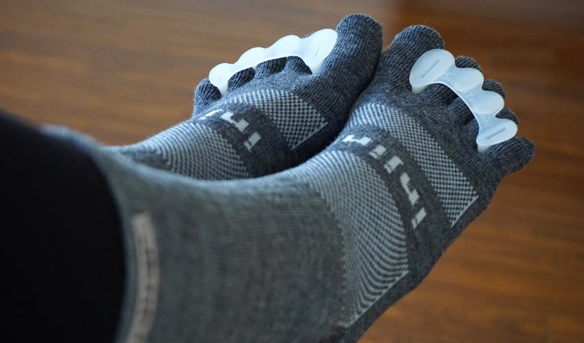 A pair of Correct Toes Original toe spacers being worn over top of Injinji Crew Wool Charcoal toe socks