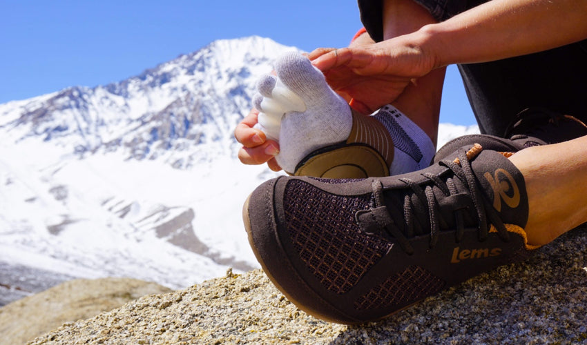 A hiker in Lems Primal 2 Brown shoes putting on a pair of Correct Toes toe spacers