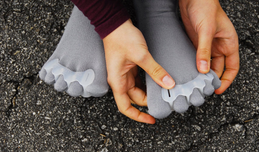 Correct Toes user applying the device while seated on pavement