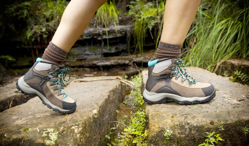 A hiker wearing thick-soled hiking boots and stepping from one stone to the next