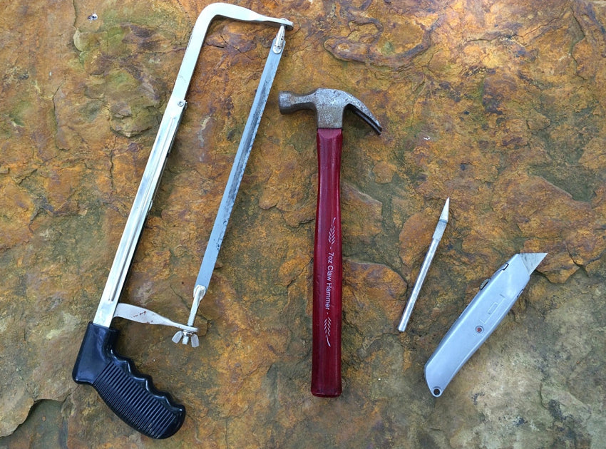 A hacksaw, hammer, scalpel, and utility knife placed on a stone step