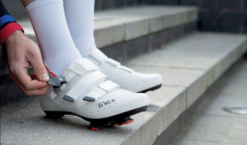 A cyclist, seated on concrete steps, securing the strap of a conventional cycling shoe
