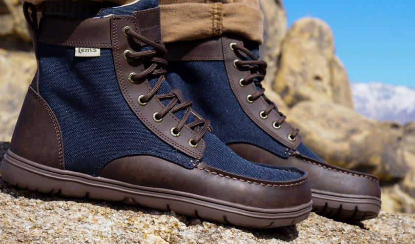 Close up view of a pair of Lems Boulder Boots in Navy Stout with rocky outcroppings and snowy peaks in the background