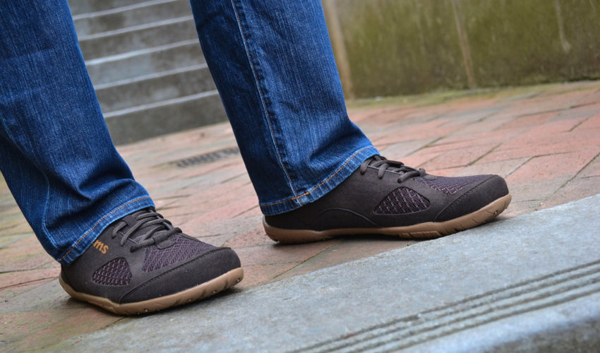 A person standing on cobblestones and wearing Lems Primal 2 Brown shoes