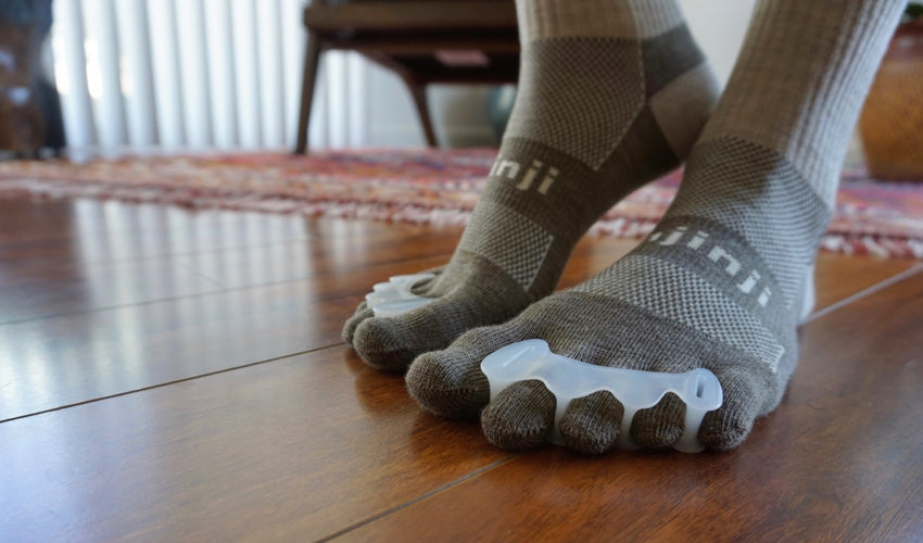 A person wearing Correct Toes and Injinji toe socks on hardwood floors