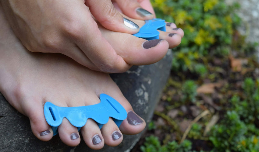 A close-up view of a person in a garden setting putting on a pair of Correct Toes Aqua toe spacers