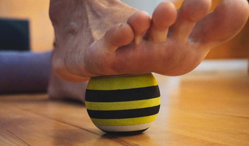 The underside of a foot that's resting on a massage ball