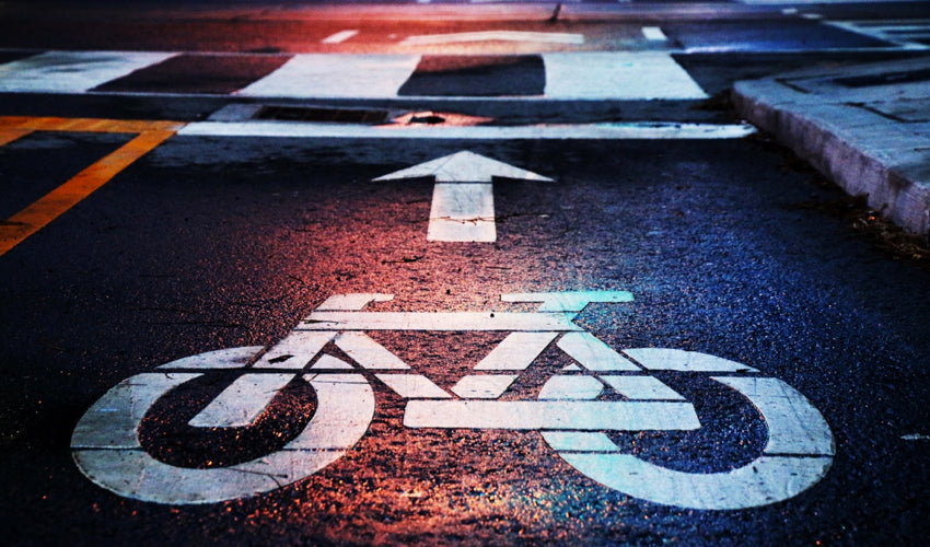 Bike symbol and arrow, in a commuting lane, on damp pavement at dusk