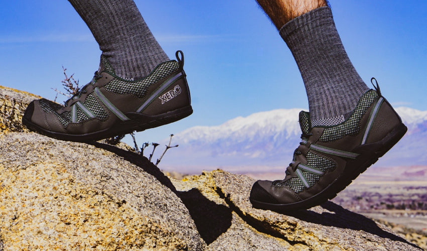 A side view of Xero TerraFlex athletic shoes worn by a trail runner with mountains in the background