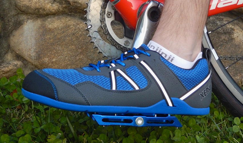Side view of a cyclist wearing Xero Prio athletic shoes and using Blue Catalyst Pedals