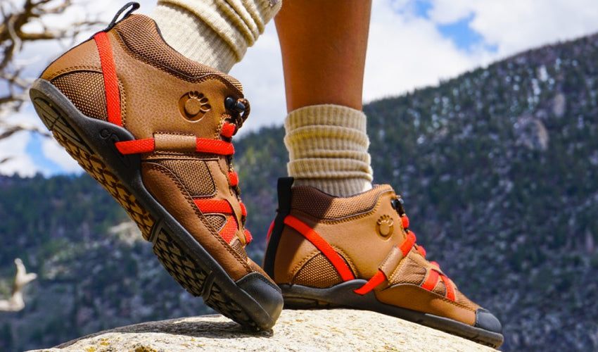 Side view of the feet of a hiker wearing Xero DayLite Hiker hiking boots