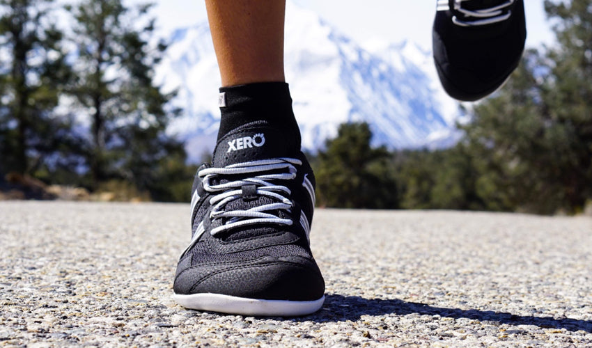 A head-on view of the toe box of a pair of Xero Prio athletic shoes worn by a road runner