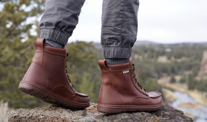 A hiker wearing Lems Boulder Boots in Leather Russet with a river and valley in the background
