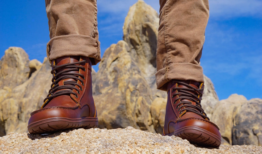Hiker wearing Lems Boulder Boots in Leather Russet with rock formation in the background