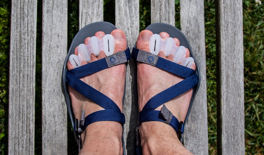 A top-down view of a pair of feet wearing Correct Toes and Xero Z-Trek sports sandals