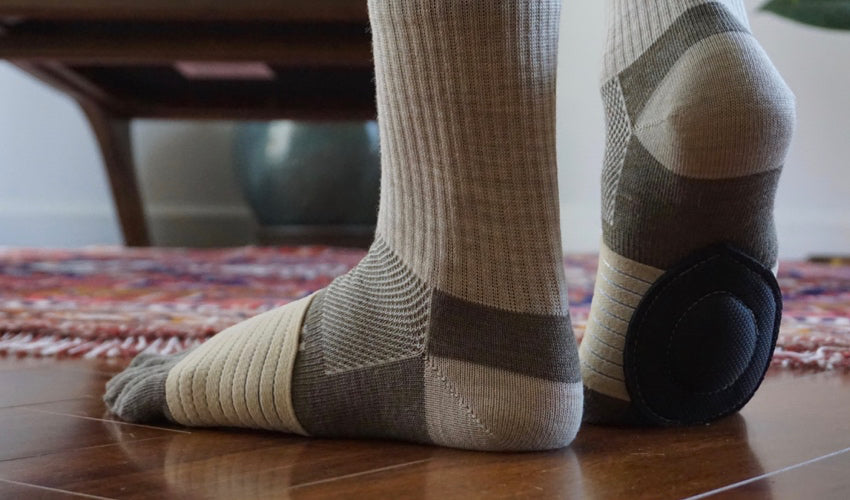 A person wearing Injinji toe socks and Strutz foot pads indoors