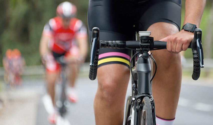 Head-on view of a road cyclist pedaling his bike with competitors in the background