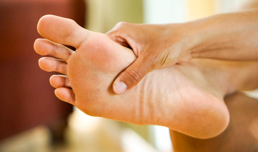 A person using their hand to assess the sole of their flat foot