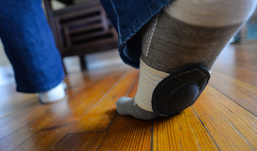 The underside of a pair of Strutz foot pads being worn by a person walking indoors on a wood floor