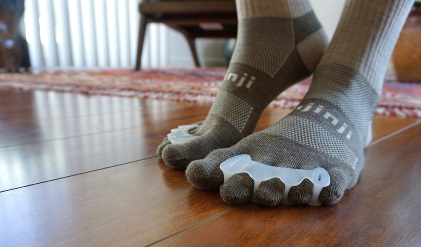 A close-up shot of a person wearing Injinji toe socks and Correct Toes toe spacers and standing on a hardwood floor