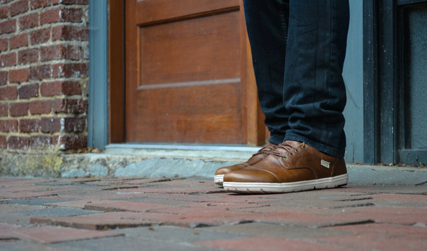A person on a brick cobblestone street wearing Lems Nine2five dress shoes in Coffee & Cream