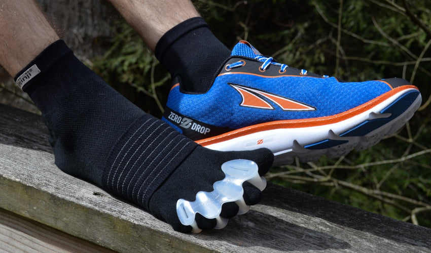 An athlete wearing Altra athletic shoes, Correct Toes toe spacers, Injinji toe socks, and Strutz foot pads