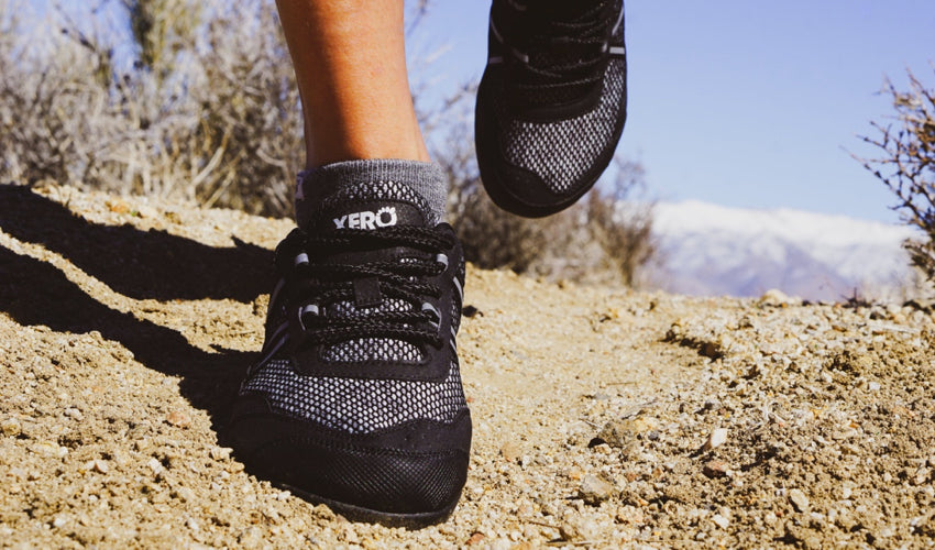 Trail runner in mid-stride wearing Xero TerraFlex Black athletic shoes