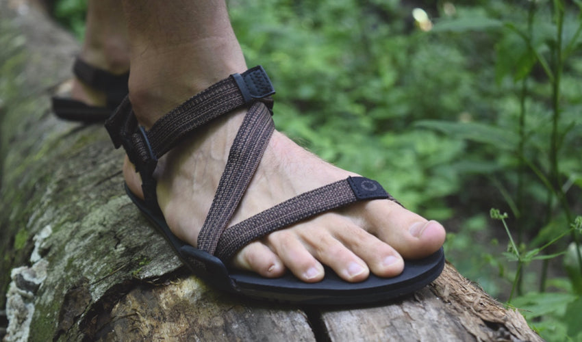 Man wearing Xero Z-Trail sports sandals and standing on a log in the forest