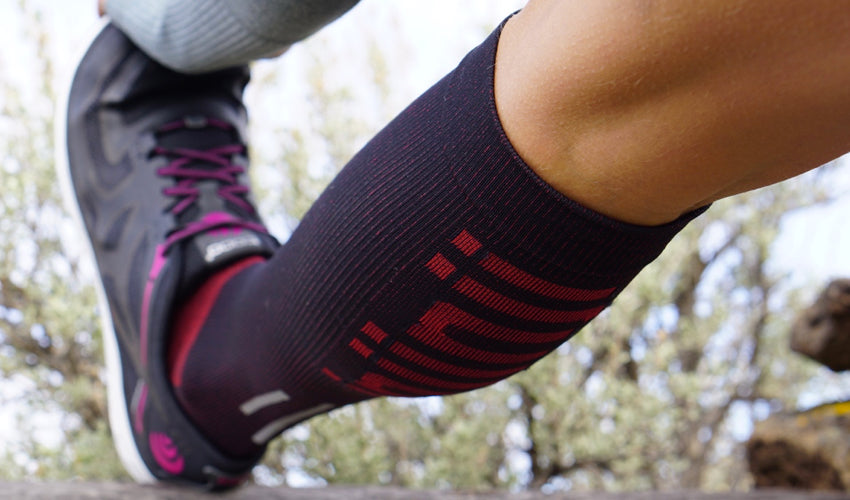 An athlete wearing Injinji compression toe socks and stretching out her hamstring