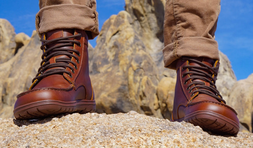 A person posing in a pair of Lems Boulder Boots in Leather Russet with blue skies and interesting rock formations in the background