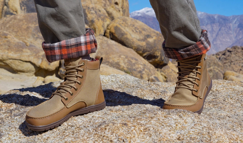 Hiker striding over rocks wearing a pair of Lems Boulder Boots in Brown