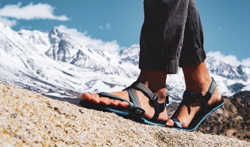 A striding hiker, in the mountains, wearing Xero Z-Trail athletic sandals