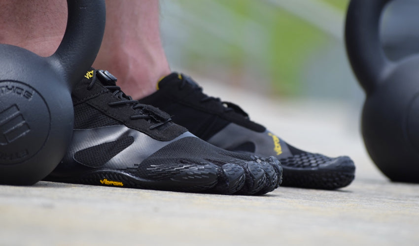 A side view of Vibram FiveFingers KSO shoes worn by an athlete using kettlebells