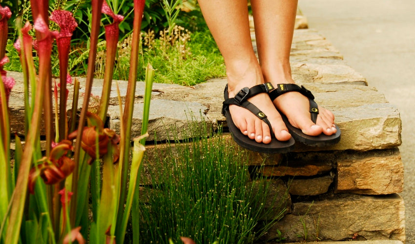 Female wearing Luna Mono 2.0 sandals while standing on a low stone wall and posing among vibrant plants in an arboretum