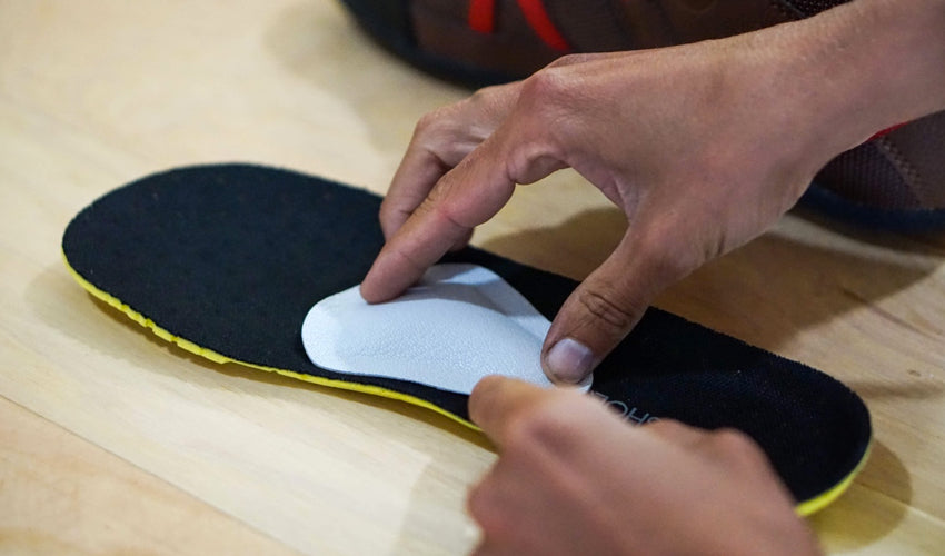 A set of hands making positional adjustments to a Pedag metatarsal pad situated on top of a shoe insole