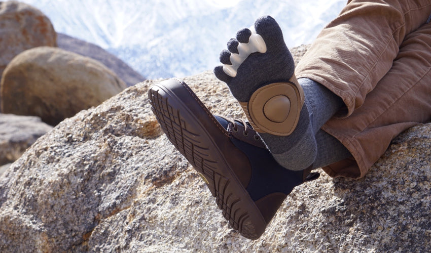 A seated hiker displaying Correct Toes toe spacers, Strutz foot pads, Injinji toe socks, and Lems Boulder Boots