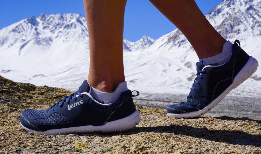 A hiker wearing Lems Primal 2 Eclipse minimalist shoes with snow-capped mountains in the background